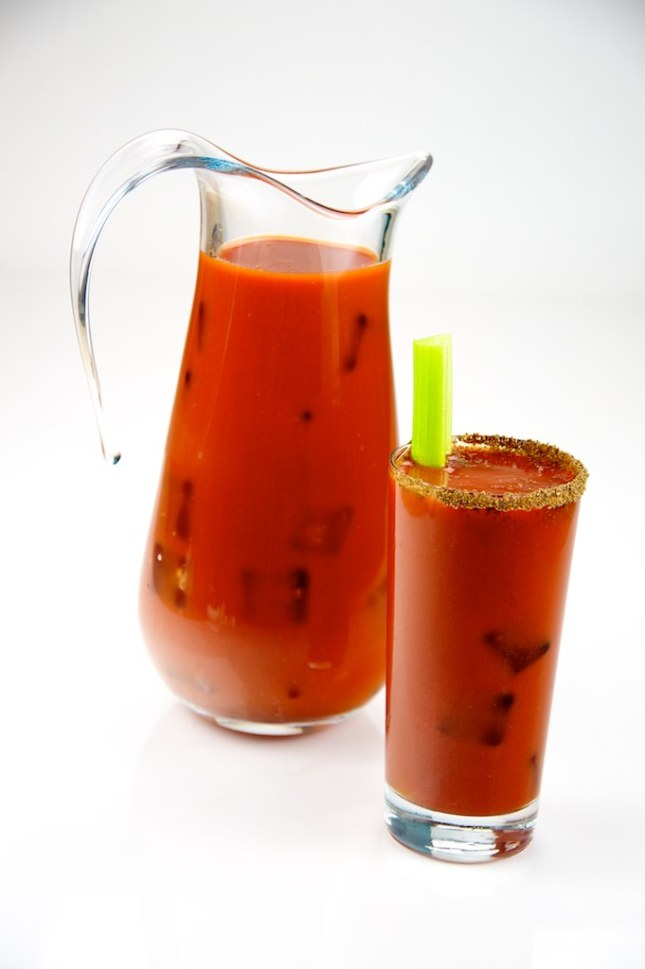 Bloody Mary Coctail with celery stalk and pitcher.