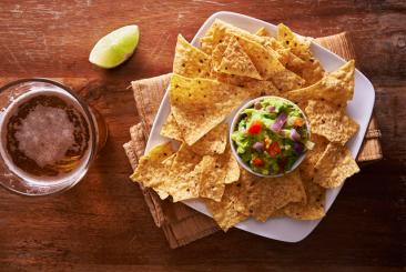 tortilla chips with guacamole and beer shot top down
