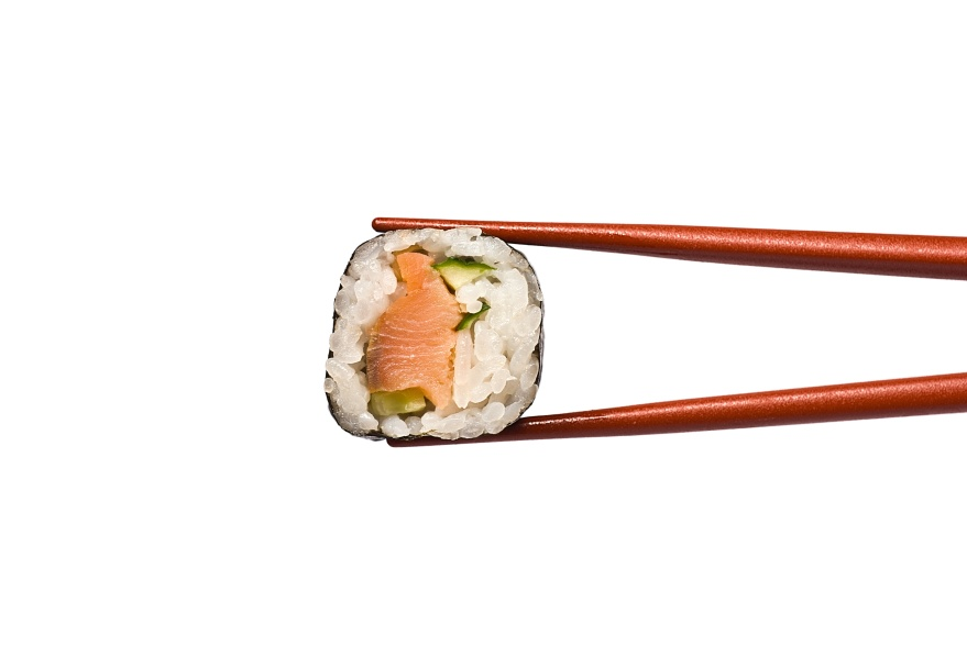 Sushi Roll is held by Chopsticks isolated on white